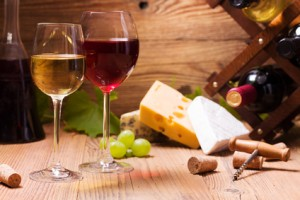 Glasses of red and white wine, served with grapes and cheese
